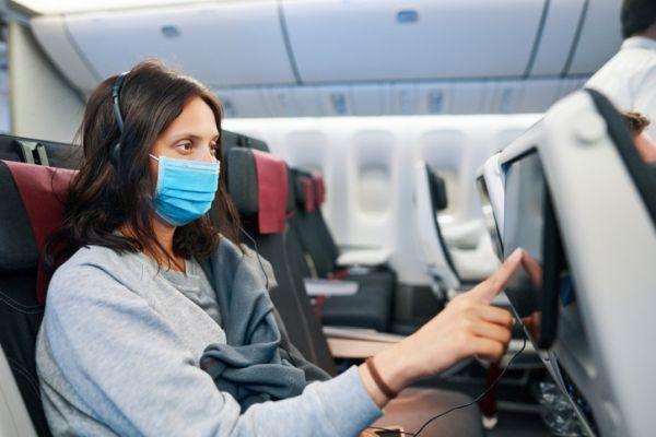 Mujer con mascarilla y tablet en avión