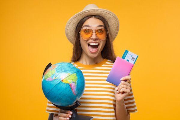 ciudades-mas-visitadas-mujer-globo-del-mundo-y-billetes-avion-istock